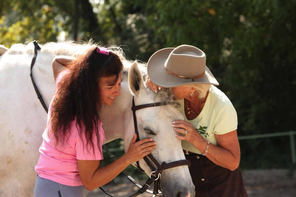 Magali Delgado and Linda Tellington-Jones perform Raccon TTouches on one of Magali's horses.