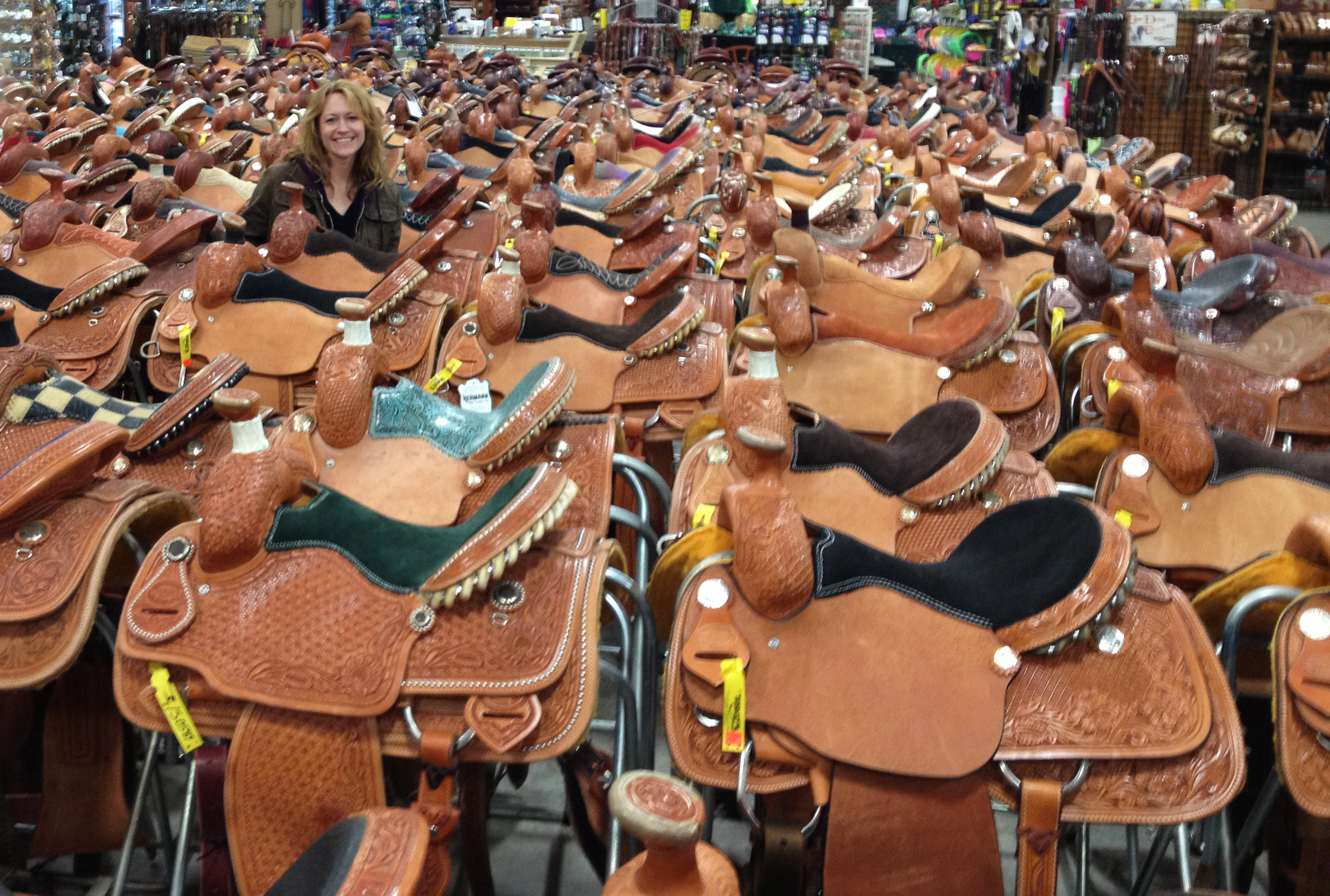 71475f9089e6 Rebecca Didier in a sea of saddles–Teskey's is known for their incredible  selection…over 1000 in stock!