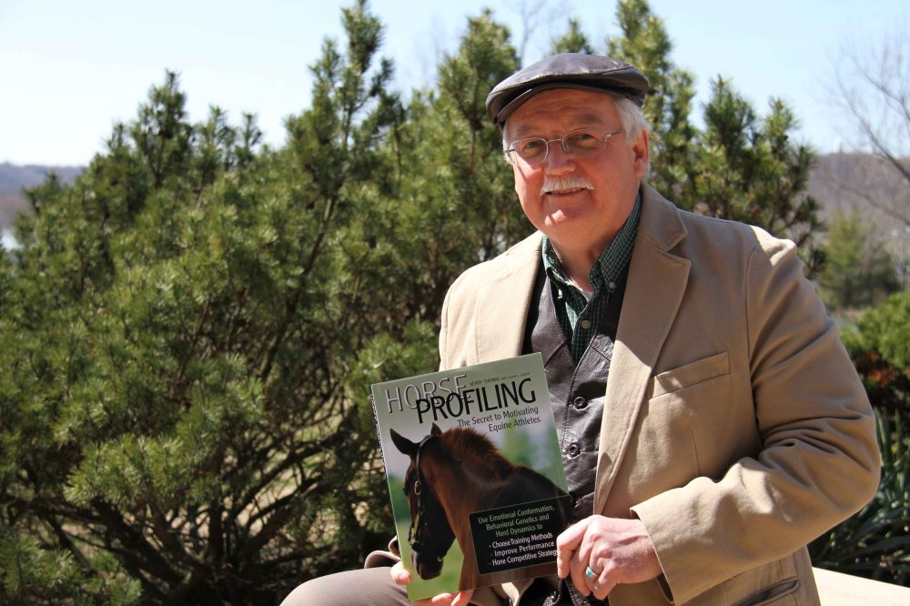 Thoroughbred pedigree analyst Calvin Carter with the book he coauthored with equine sport psychology pioneer Kerry Thomas.