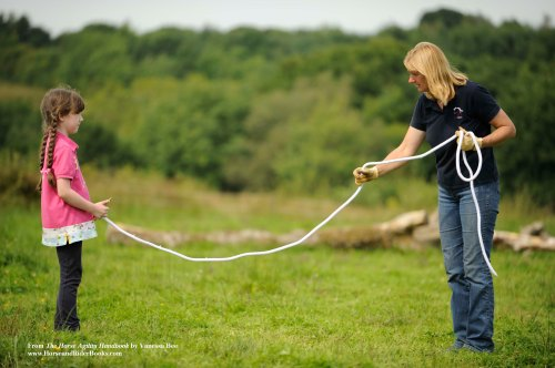 """Lucy (left) is the horse and Vanessa (right) is the handler. Vanessa """"invites"""" her """"horse"""" to walk toward her."""