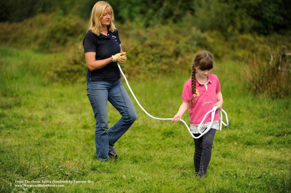 """Lucy and Vanessa switch roles. Vanessa, the """"horse,"""" closes her eyes to really feel Lucy communicating with her through the lead rope."""